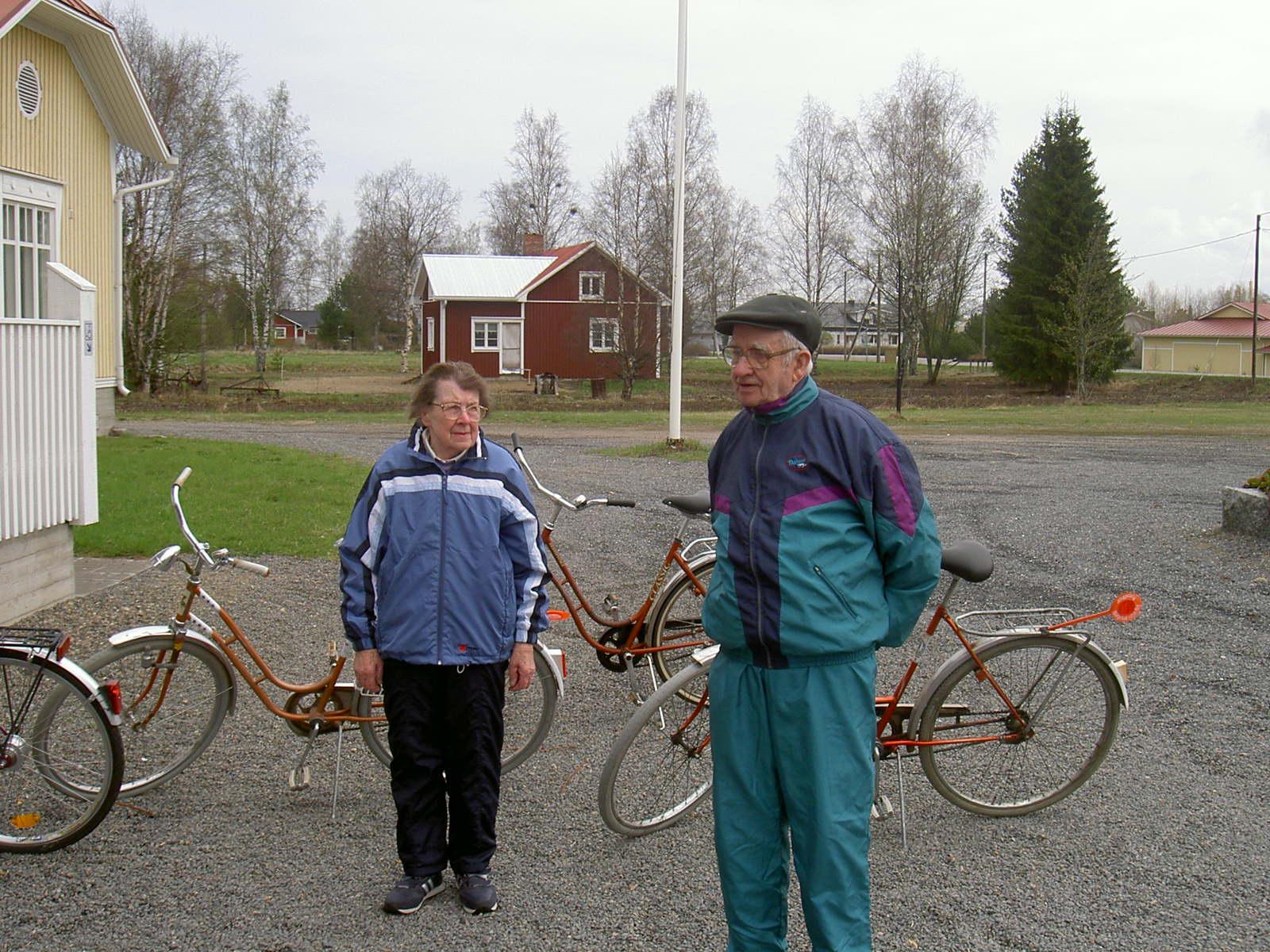 Jenny och Ragnar Backlund deltog i ungdomsföreningens cykeljippo vid Majbo år 2003. Den röda gården i bakgrunden är fröken Elin Rosenbacks gård, som har renoverats och bytts till av de nuvarande ägarna. Längst till höger Papron-huset, som år 2016 övertogs av Kerno.
