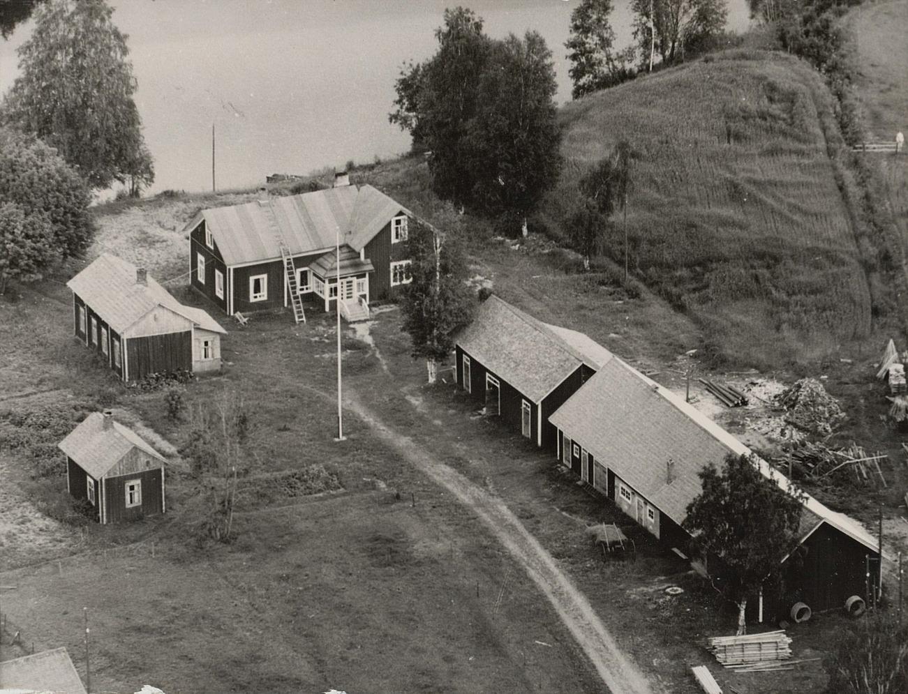 På den här flygbilden från 1960-talet så ser åkern bredvid gården ut som ett högt berg men i själva verket är det nog bara en vanlig, slät åkerplätt.