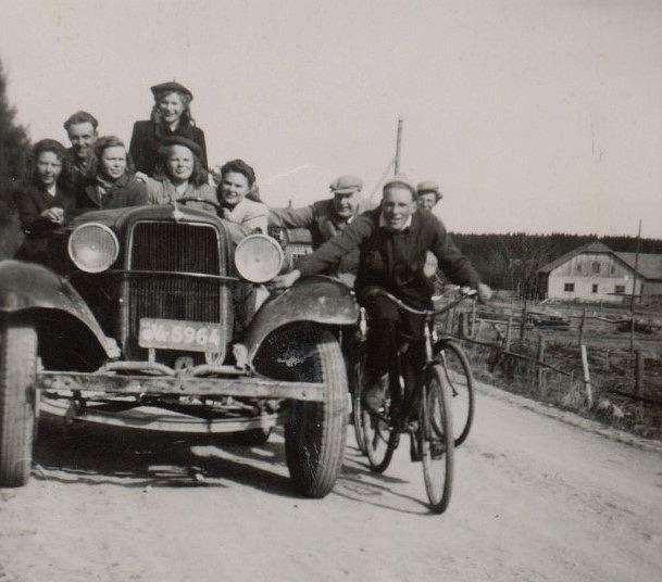 Åke Jossandts biltraktor var speciell och många ville vara med och provköra men alla rymdes inte med. Från vänster Birgit Englund, okänd man, Dagny Lillkull, stående Gunvor Hemberg och framför henne sitter systern Else-Maj och till höger sitter Greta Gröndahl. Cyklisterna från vänster är läraren Einar Lind, Bengt Gröndahl och lite skymd Åke Löfgren. I bakgrunden syns uthusen hos Hembergs.