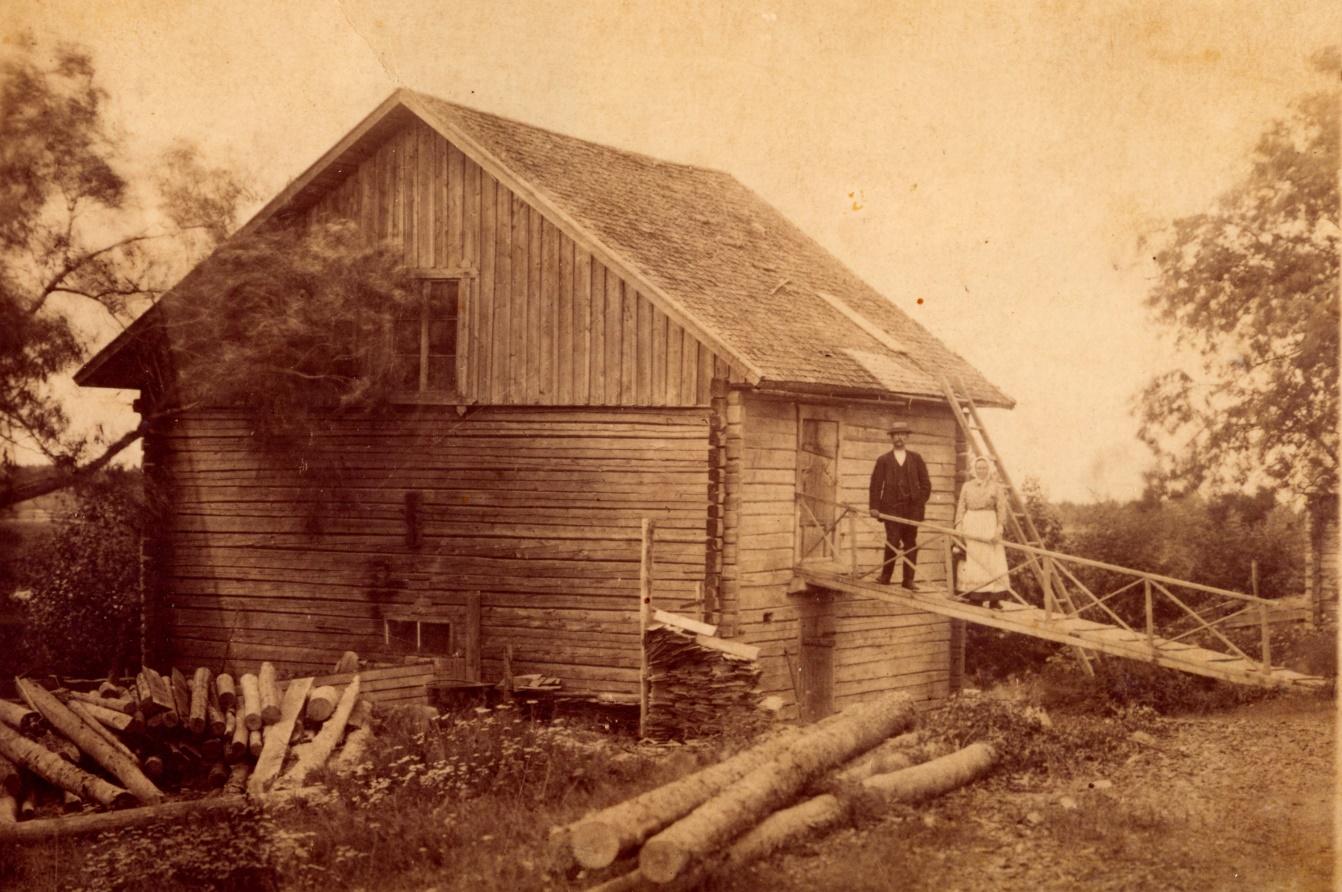 Här står mjölnaren Johan Viktor Solfvin tillsammans med hustrun Amanda på landgången till kvarnen, någon gång efter 1912. I knuten står en trave med pärtor som troligen hyvlades på samma ställe, bland annat hade Träsk Erik och en Nyman köpt pärtor år 1916.