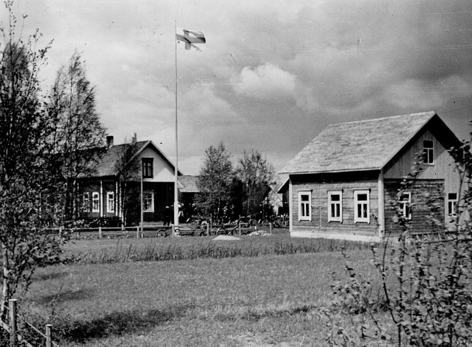 """Där """"Jöranas"""" eller hos Erland Norrgård flaggades det hösten 1941 då dottern Svea gifte sig med grannen Gunnar Guss. Till höger ser vi lillstugan, alltså den dit Heikki och Ulrika Henberg flyttade i november 1907. Troligen hade lillstugan tidigare stått på en annan plats på samma tomt. Här ser vi att lillstugan som bäst skarvas i både på gårdssidan och med större vindsutrymmen, då Erland och Ida Norrgård flyttade in."""