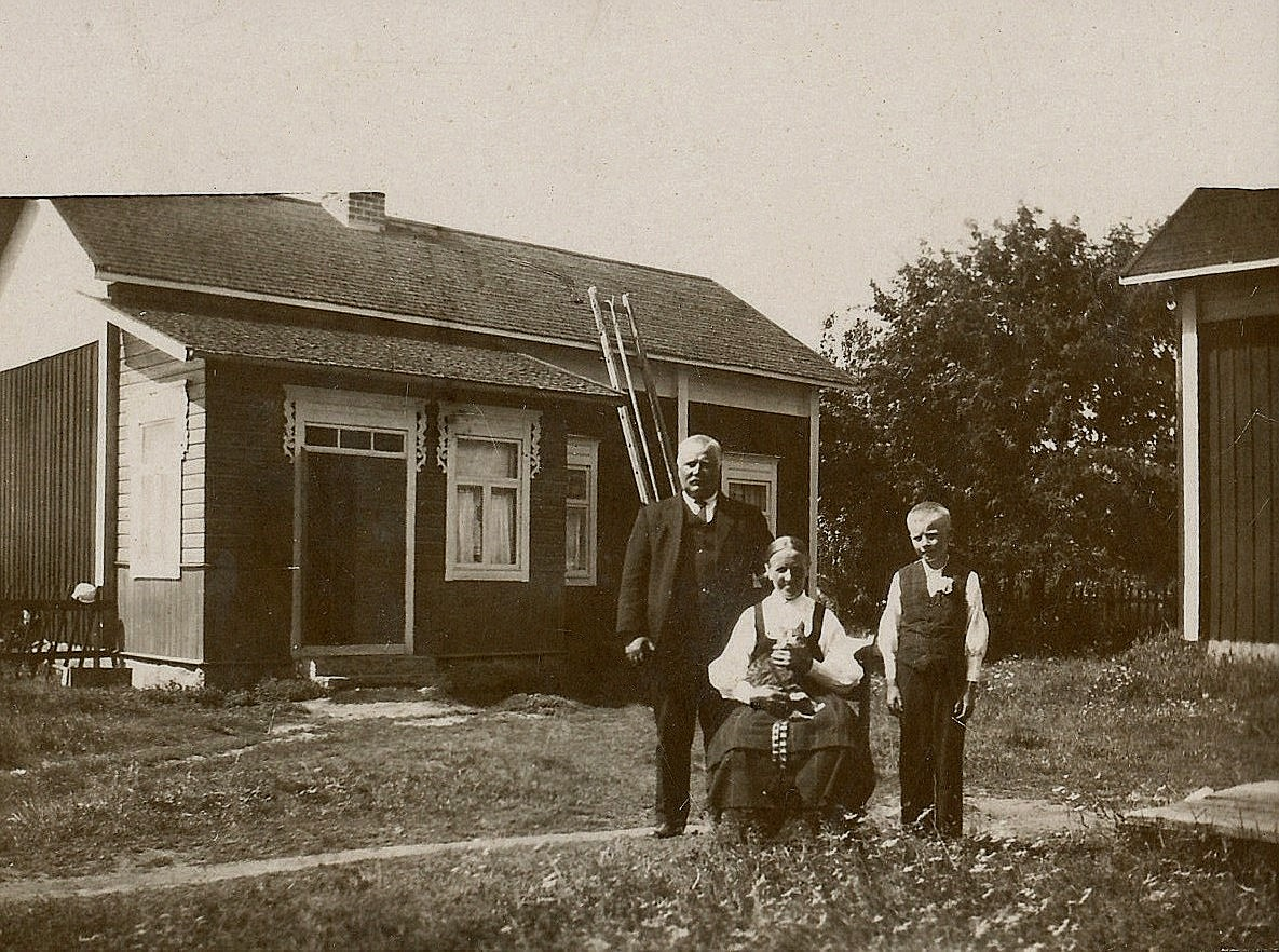 Josef och Maria Backlund framför sin lillstuga tillsammans med barnbarnet Eskil. Notera pottan på staketet till vänster.
