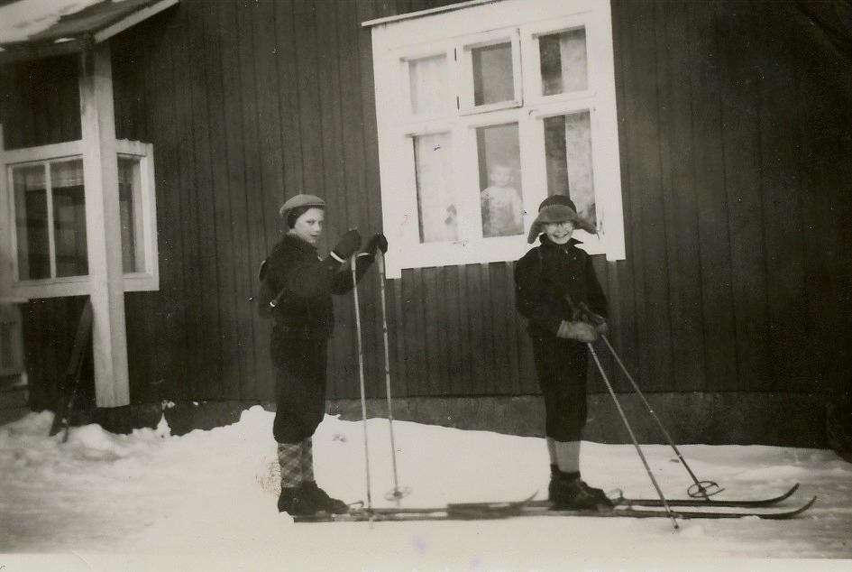 Vintertid förkortades vägen till skolan betydligt då det gick att skidande snedda över Klemets åkrarna. Per-Erik först och Henry Rosenback från Bergåsen, som var en duktig skidåkare kommer efter. Lillabror John tittar i fönstret.