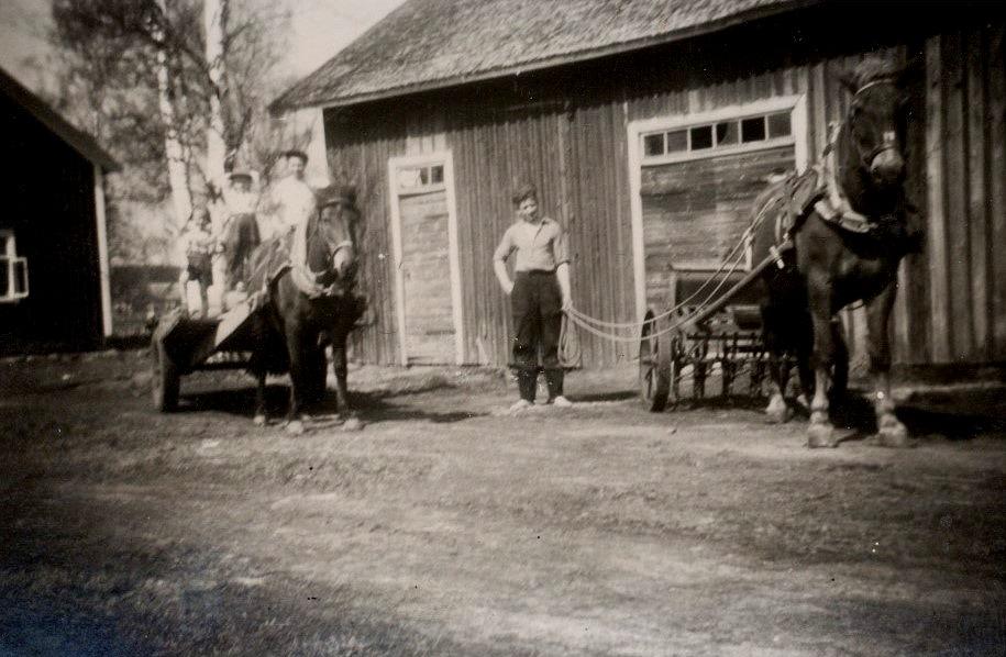 Ragnar håller i tömmarna på Linda medan brodern Åke står på Puttes kärra tillsammans med några barn.