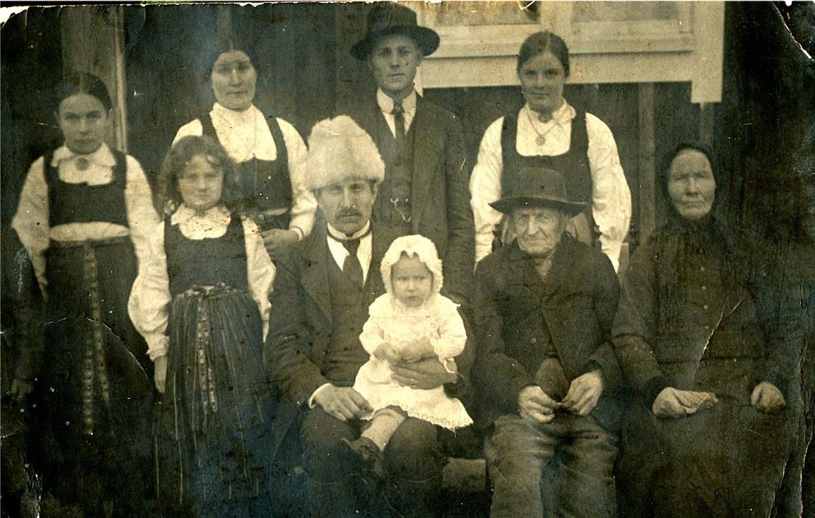 """På det här fotot från 1920 som Börje Viklund lånat ut sitter Axel Forslin i mitten med Mildrid (f. 1919) i famnen. Bredvid honom till höger sitter hans föräldrar """"Lillkårk-Josip"""" och Anna Kajsa. Stående från vänster Ellen (f. Grönroos 1906, gift med Yrjö Pullola (1907-1949), Ellen dog 1988. Hon var dotter till """"Andersas""""-Erland Grönroos men bodde hos sin farmor och farfar i lillstugan hos Forslins). Bredvid Ellen står Axels dotter Ines (1912-1993), sedan Axels hustru Selma (1891-1937) . Den unga damen högst upp till höger var en tjänarinna hemma från Västervik i Ömossa och hennes pojkvän bredvid."""