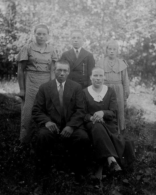 Här sitter Erland Storkull tillsammans med sin andra hustru Martha och bakom står barnen Elin, Arvo och Impi.