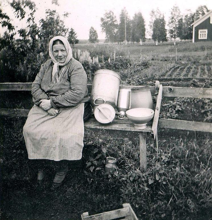 Hilma Sandbacka ser nöjd ut då mejarkannon, mjölkkannon, mjölkämbaret och mjölksilen är urtvättade. I bakgrunden syns litet av Valter Långfors gård.