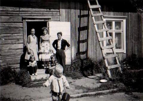 I dörröppningen står Martta och dottern Onerva och hennes man Voitto Pihlajamäki, som var från Kauhajoki. På trappan sitter Hannele och Allan och flickan längst fram är Onervas dotter Lena. Huset i bakgrunden är det som Hemming byggde i början på 30-talet i Nystad och detta foto är taget ungefär 1960.