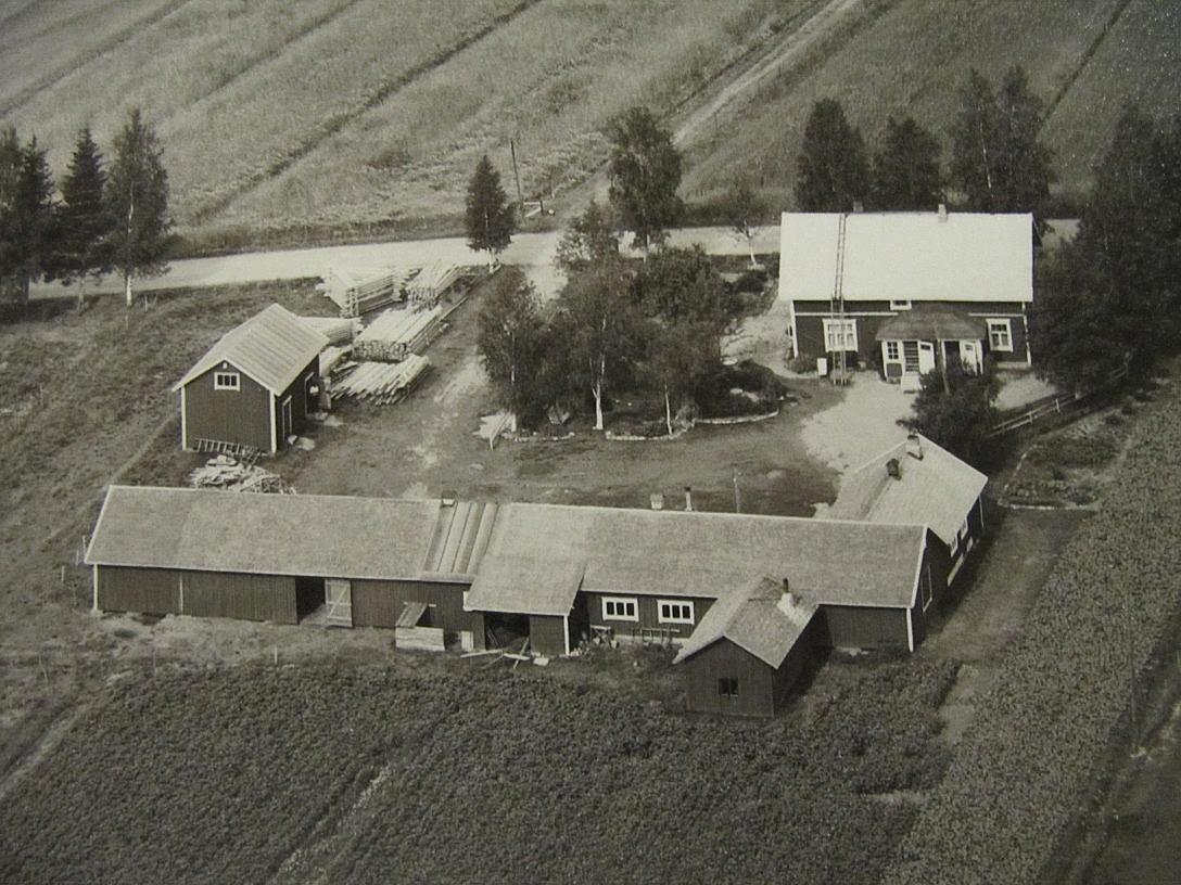 Den här flygbilden är från år 1961 och Myllyniemis gård uppe till höger. Den högra ingången gick till snickeriet och den vänstra till Johannes och Sylvias bostad. Snickarvirket finns upplagrat nära landsvägen. Åkervägen på andra sidan Åbackvägen leder till Oskars gård, som revs år 1961.