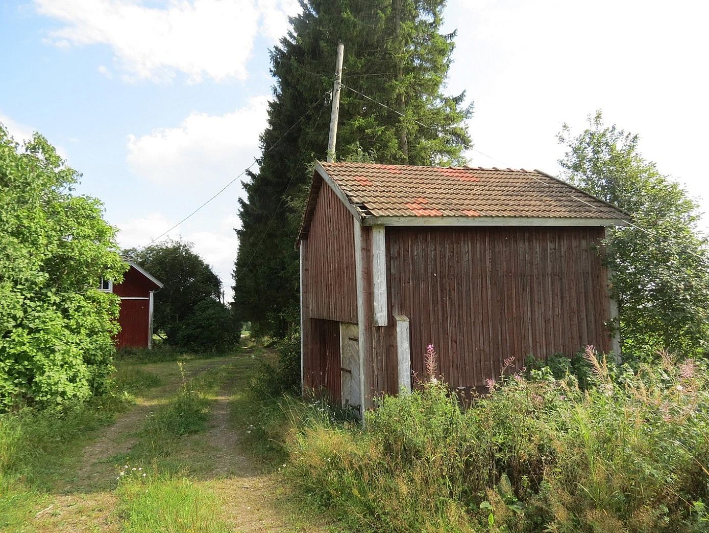 Detta gamla härbre stod tidigare nere i byin, men flyttades i samband med storskiftet år 1906 till en plats inne på gården. I slutet på 1930-talet rullades det iväg till denna plats, pöllien päällä. Pauli Hällback minns berätta hur förvånad han var en dag då han kom hem från skolan och märkte att härbret var flyttat. Johannes hade nog haft hjälp av någon av sina bröder med flyttningen. Huvudbyggnaden i bakgrunden, fotot 2014 taget från norr.