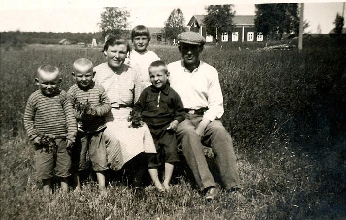 """Här sitter hela Santamäkis familj i gräset på Åbackan och i bakgrunden syns """"Åsinas-Viktoras"""" alltså Viktor Rosenbacks gård som i slutet på 20-talet övertogs av Anselm Viklund då han återvände från Amerika."""