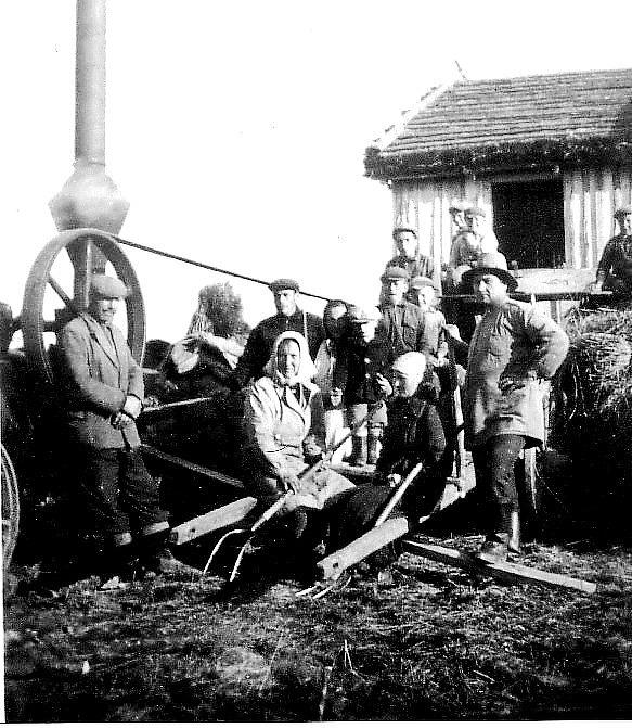 Så här kunde det se ut då det var tröskningstalko i Dagsmark. På bilden från ca 1940 står Johannes Hällback t.v. och lutar sig mot ångmaskinens remskiva som drog tröskverket. Mitt i bild sitter mor Hilma med sonen Pentti Hällback och längre bak står Penttis bröder. Mannen t.h. heter Paavilainen och han var hemma från Alakylä i Bötom. Fotot är taget bakom den stora ladan som står och lutar på den övre bilden. Det här tröskverket och ångmaskinen hade Johannes i bolag med Valdemar Rosengren köpt av ett tröskandelslag nere i Dagsmark. I Kauhajoki gjordes ångmaskinen om och på skorstenen byggdes ett gnistskydd som syns i nedre delen av skorstenen. Men när de fick 3-fas elektricitet till Åbackan anskaffades en Strömberg elmotor och ett riktigt Sampo Rosenlew tröskverk. Efter en tid löste Johannes ut Valdemar ur andelslaget och tröskverket och elmotorn finns ännu i behåll hos Hällbacks.
