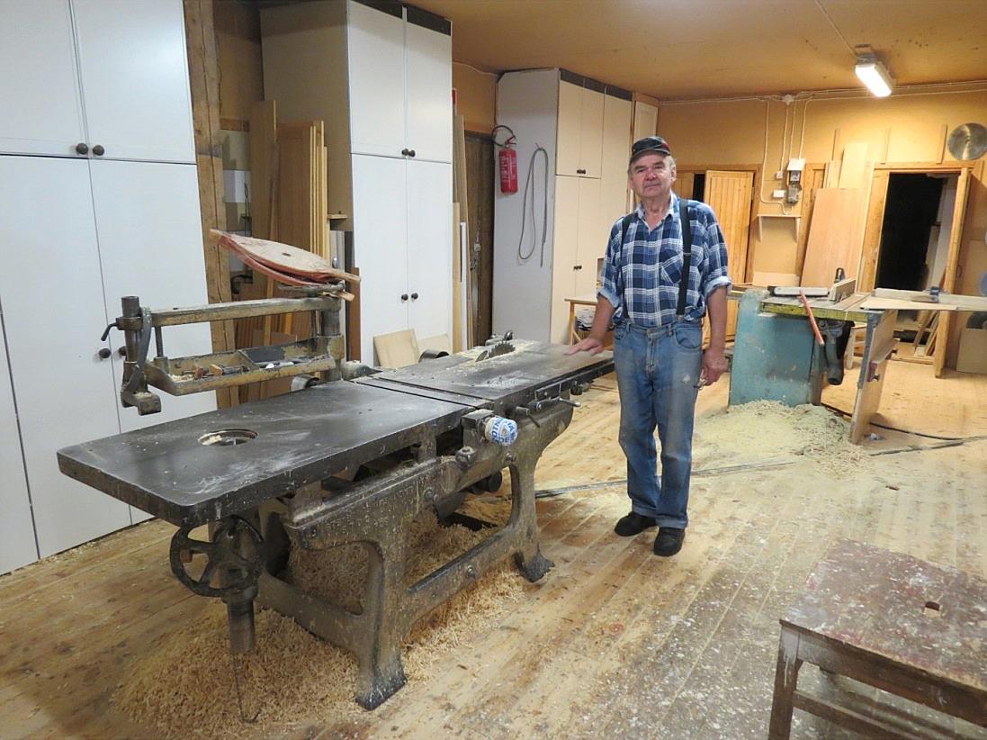 Här på bilden en stolt snickare Ilpo med maskinen som är samtida med snickaren själv. Ilpo vet att maskinen kommer att fungera ännu i 100 år, så robust och välgjord som den är.