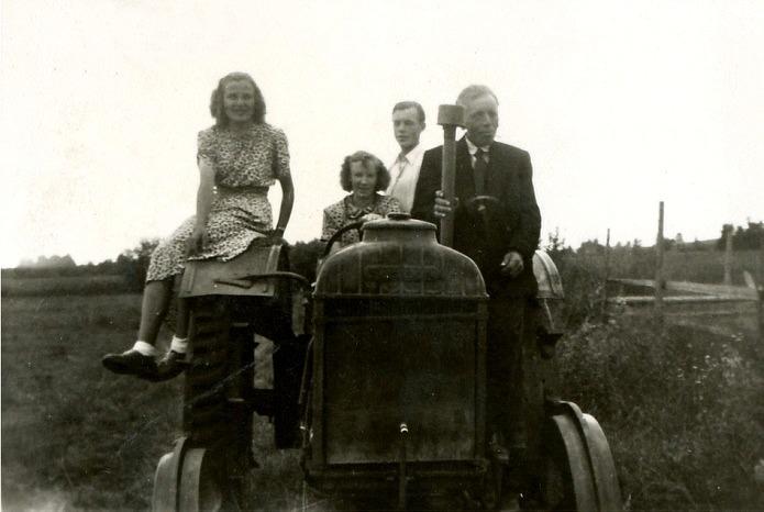 Här poserar 4 ungdomar på Mittsas Fordson-traktor som råkade stå nära vägen, från vänster Helvi Klemets, Frida Klemets, Nils Klemets och till höger står Frans Storkull.