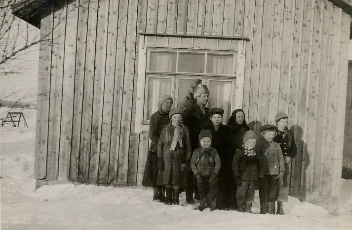 På detta foto från år 1935 ser vi nästan hela Hällbacks familj, där de står utanför lillstugan som byggdes ungefär 1932 och som sedan på 1940-talet byggdes i med en port, ett kärrlider och ett vedlider. Längst bak fr.v. Hilma och Johannes Hällback, Hilmas mor Amanda Uusitalo och längst till höger Sylvi Hällback. Flickan och pojken i mittersta raden är Elvi och Alvar Hällback. I främre raden Aarre, Pauli och Jarl. Minstingen Pentti var inte född ännu när detta foto togs.