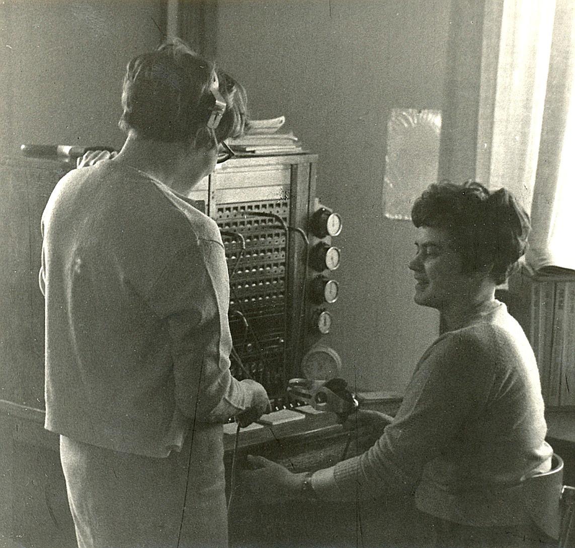 Inger Viklund sitter vid centralbordet och Annel Nyholm står bredvid. Bilden från tiden i Sparbankens hus.
