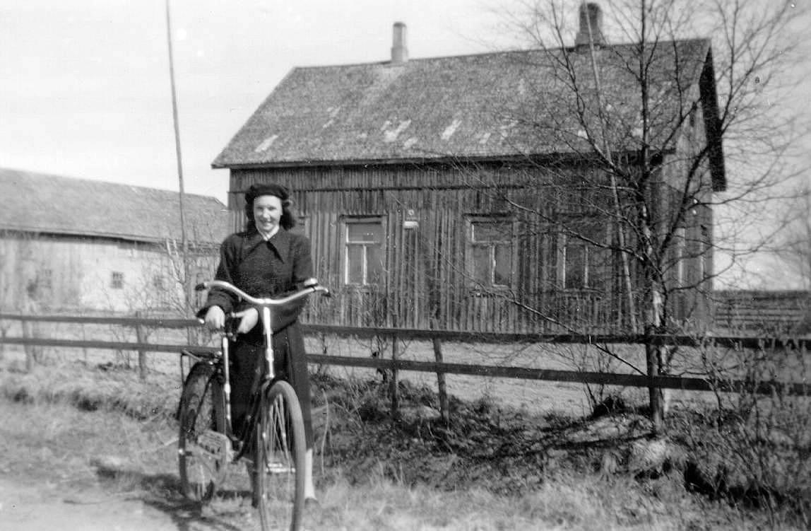 Här på bilden står Frida Klemets med sin cykel framför Frans Storkulls gård på Åbackvägen, där hon arbetade som piga.