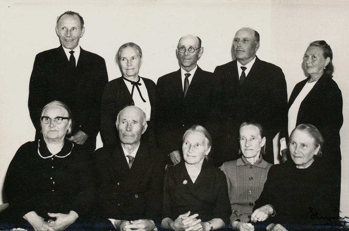 Nere t.v. Alvina (1889-1982) som gifte sig med Erland Rosenback , följande Johannes (1891-1970) som gifte sig med Hilma Elvira Ojanperä från Storå och som tog namnet Hällback, Maria Vilhelmina (1893-1989) som gifte sig med Sigfrid Storlåhls från Måston eller Lillsund, följande Alma (1895-1984) som gifte sig med Emil Nyberg och längst ut Amanda (1897-1985) som gifte sig med Evert Gröndahl. Stående fr.v. Viktor (1899-1981) som först varit gift med Helmi Tuominiemi men som sedan gifte sig med Selma Nyberg och som tog namnet Berglind, följande är Jenny (1901-1976) som var ogift, följande Leander (1904-1972) som gifte sig med Selma Hammarberg, sedan Arthur (1905-1985) som gifte sig med Helmi Lydia Jansson från Storå och längst t.h. Mathilda (1908-1984) som gifte sig med Emil Lillsjö.