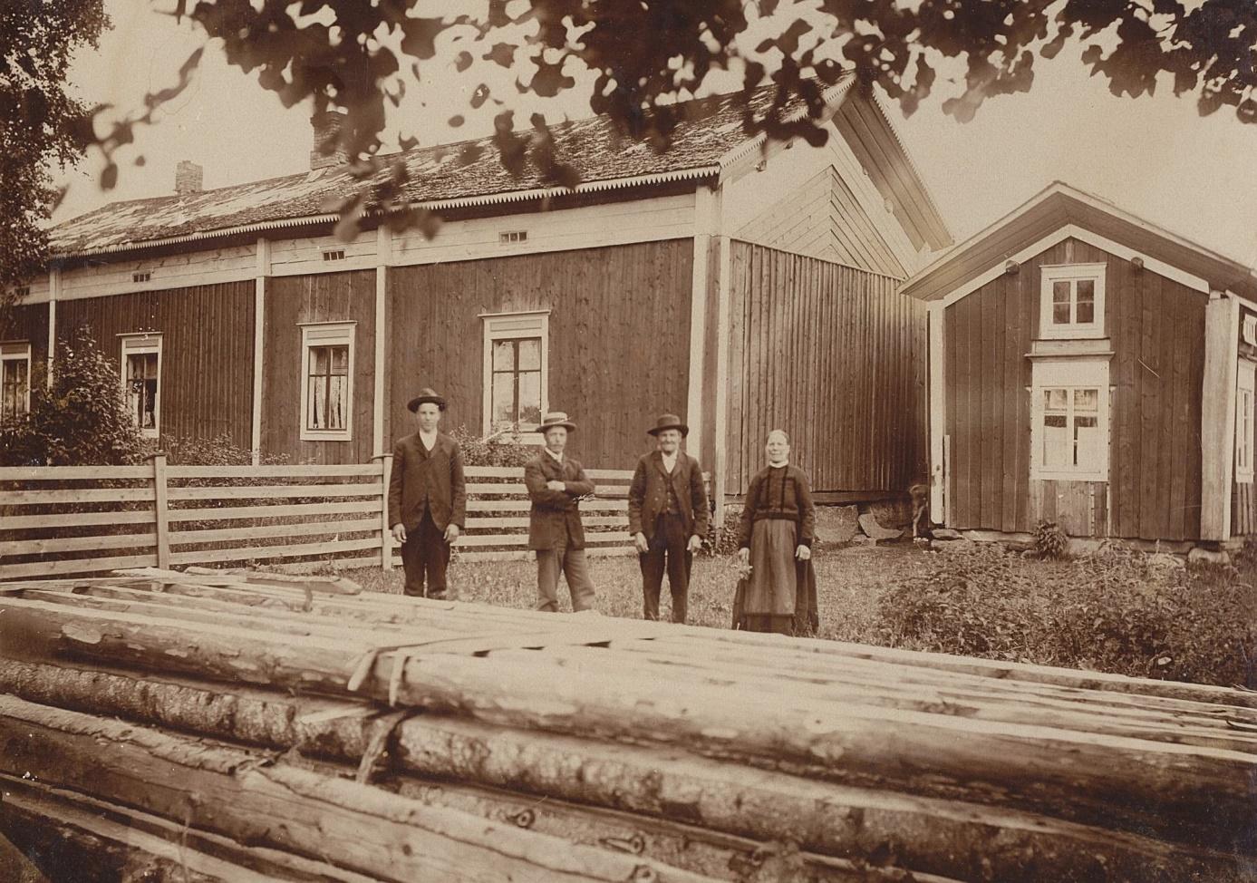 """Så här såg Koll-gården på Kårkbackan ut år 1908 fotograferad från väster av Viktor Nylund. På fotot Viktors bröder byggmästaren Emil Storkull och den blivande bonden Erik Anders som år 1910 bytte namn till Englund. Till höger husbonden """"Koll-Josip"""" och hans Anagret. Virket i förgrunden skulle användas på det nya stället i Palon."""