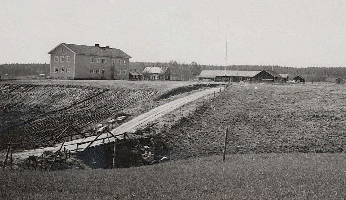 Här har Ilpo Myllyniemi lyckats fånga många saker på samma bild. Fotot är från senare hälften av 50-talet, där den finska folkskolan dominerar. Till höger om skolan syns Johannes Myllyniemis gård, medan uthusen till höger finns hos Knut Santamäki. Bron och väger leder till Frivelas eller Mellanå som det heter nuförtiden.
