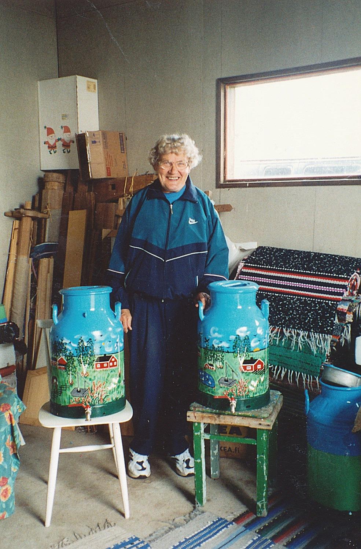 Här står Helvi Klemets år 2003 i uthusen där hon hade sin målarverkstad och visar upp två målade mjölkkannor med urtappningskran.