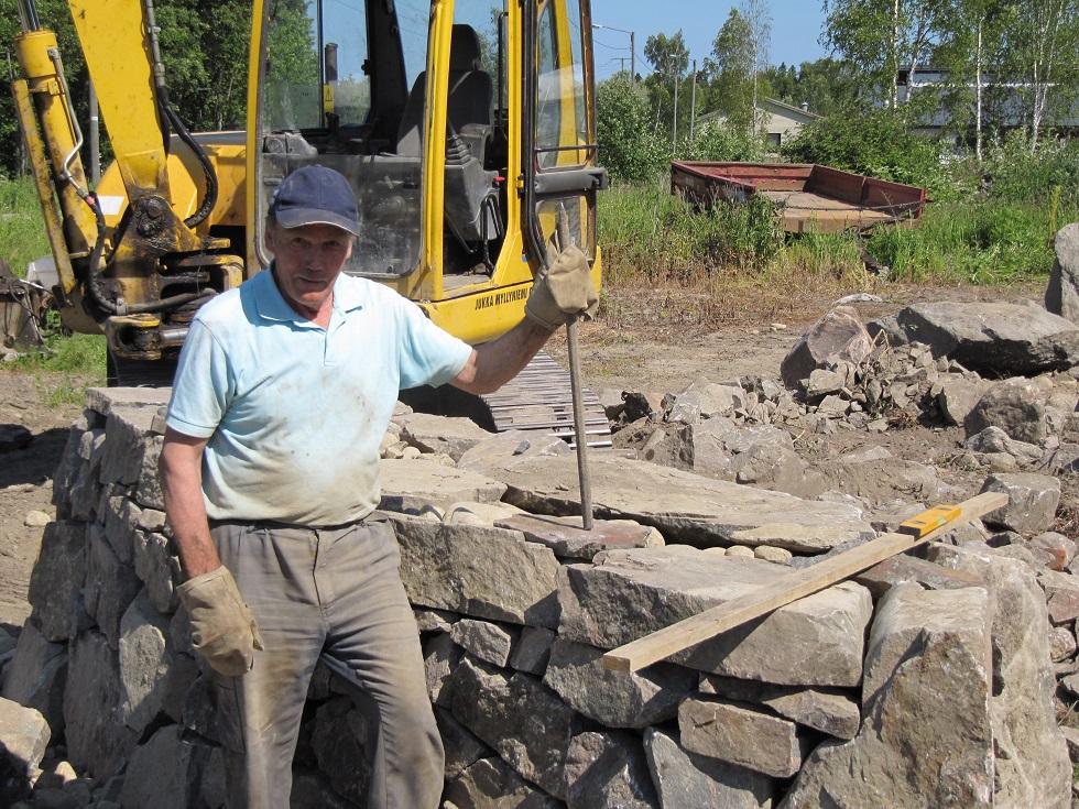 Stora stenar skall flyttas och lyftas med grävmaskin men här visar Jukka upp järnspettet som alltid skall användas för att få stenarna att ligga rätt.