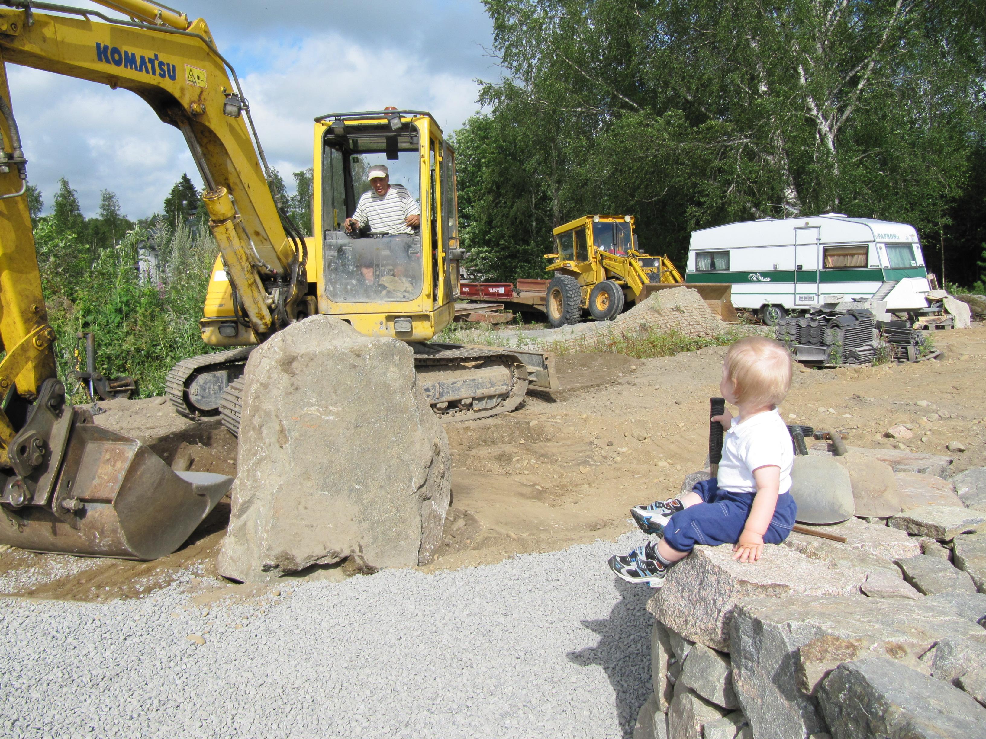 Den lilla pojken på stenmuren ser beundrande på då Jukka flyttar stora stenblock med grävmaskinen.