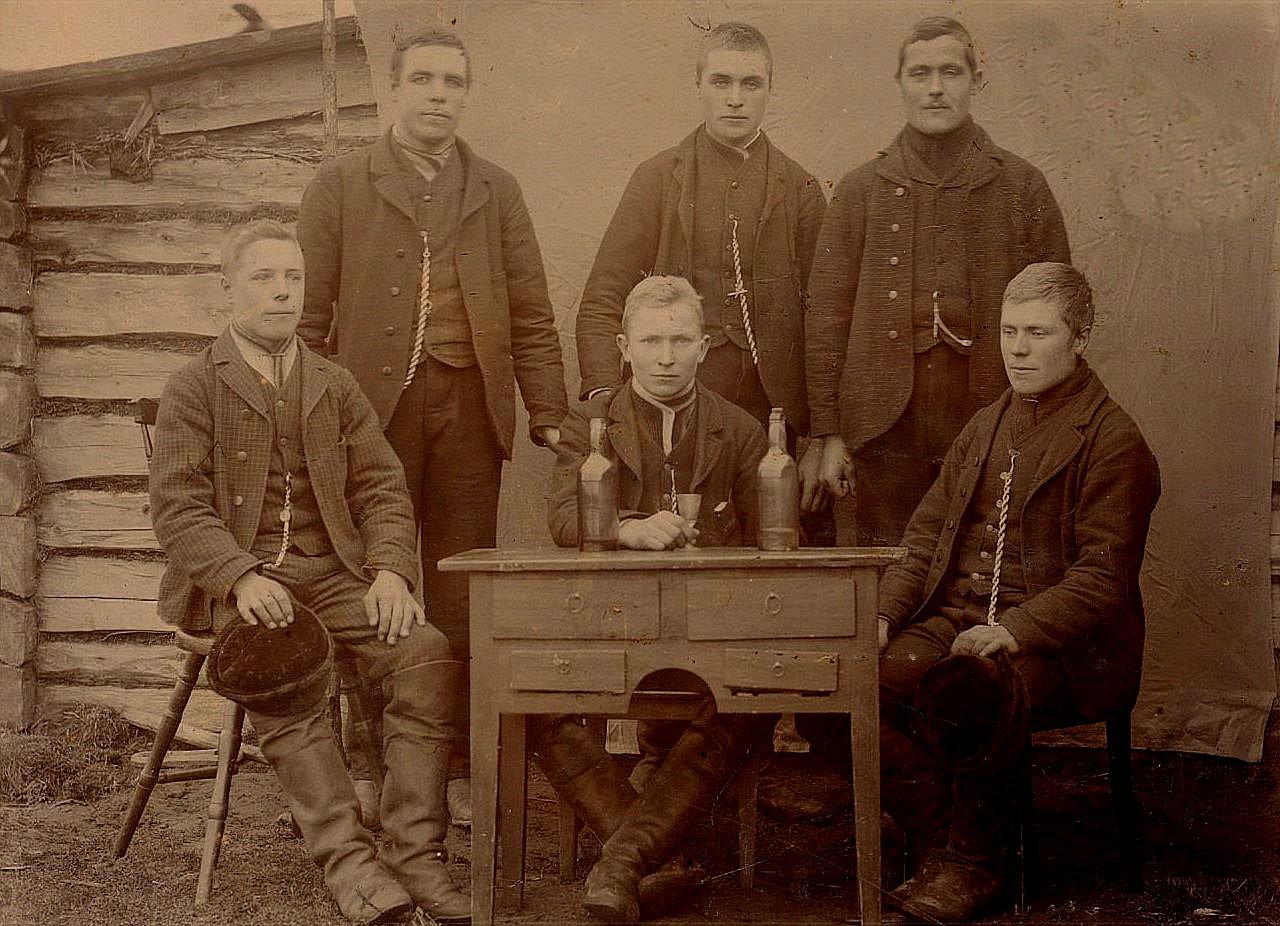 """Det ser ut som ett avskedsfest för """"Pelas"""" Otto Lillkull, som sitter bakom skrivbordet. 1903 for han till Amerika och kom inte tillbaka. Kamraterna runtomkring är från vänster Erik Ander Englund från Koll, """"Andäsas"""" Erik Anders Sundblom, """"Andäsas"""" Erland Grönroos, """"Kia´s"""" Erland Båsk och sittande till höger """"Ruffa-Josip"""" Josef Granholm."""