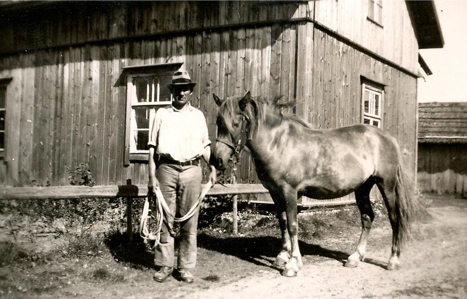 Här står Knut med hästen utanför hemmet.