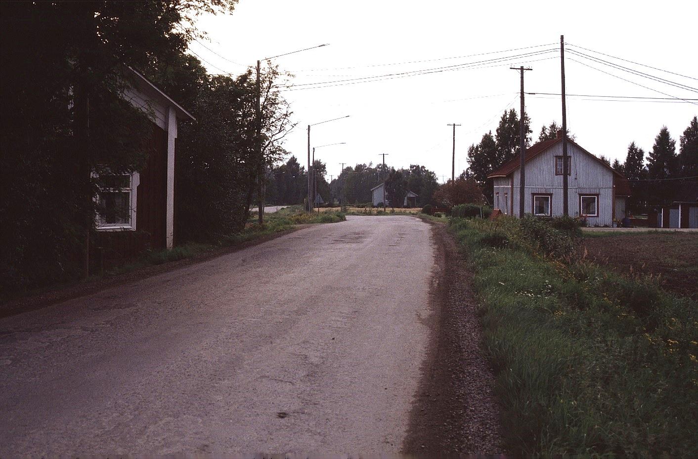 """Landsvägen utanför """"Mattas-Lennatas"""" eller """"Andersas"""" som det hette förr. T.h. Artur Lövholms gård och mitt i bild syns Kangas Velis hus. Foto 1983."""