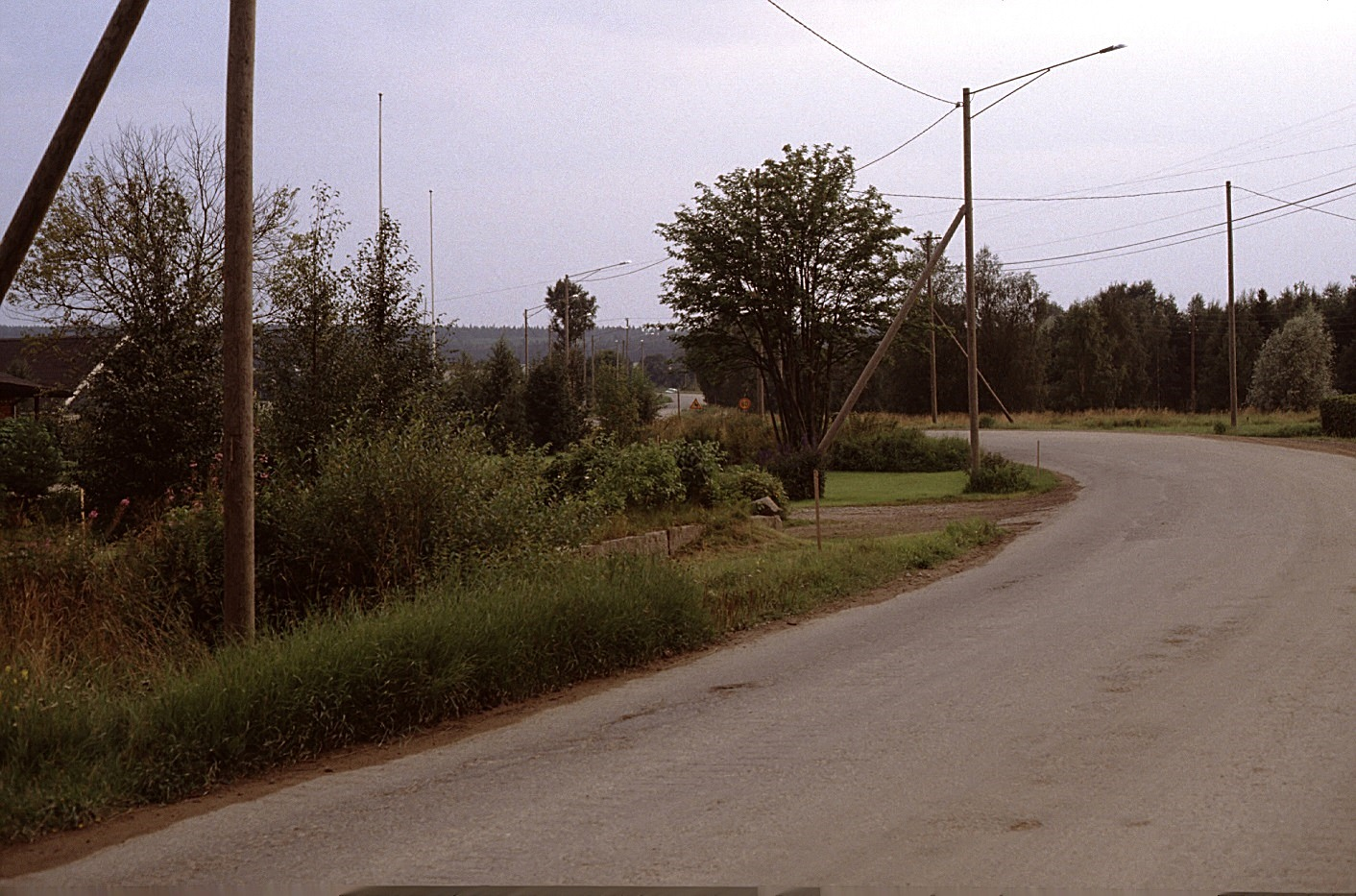 Landsvägen från Sebbas-backan söderut år 1983. Taket t.v. är på Kurt Backlunds gård och stenfoten som syns mitt i bild hörde till Noréns affärshus.