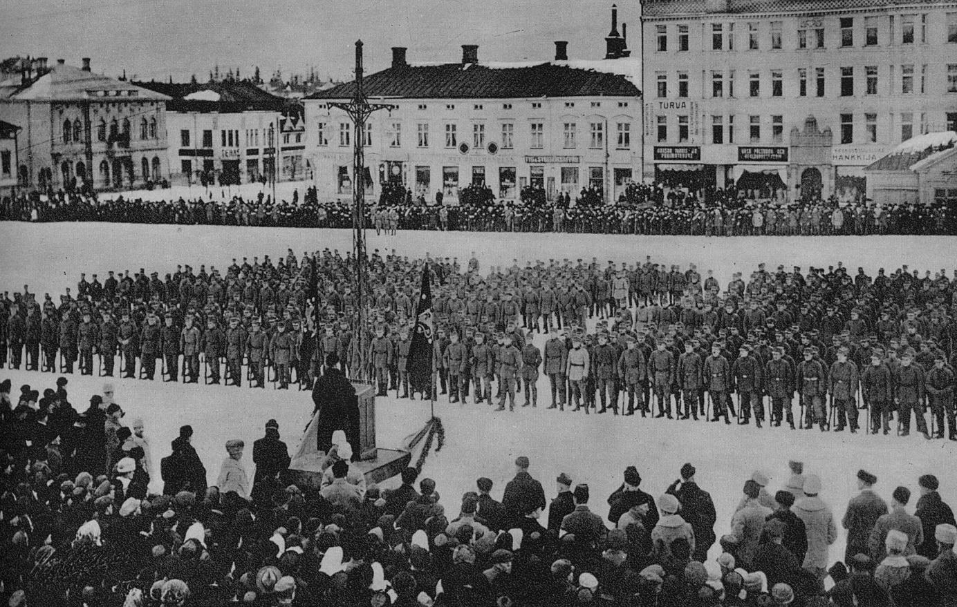 Här står jägarna på torget i Vasa den 25 februari 1918. Efter en lång färd med S/S Arcturus står de och lyssnar på senator Renvall.
