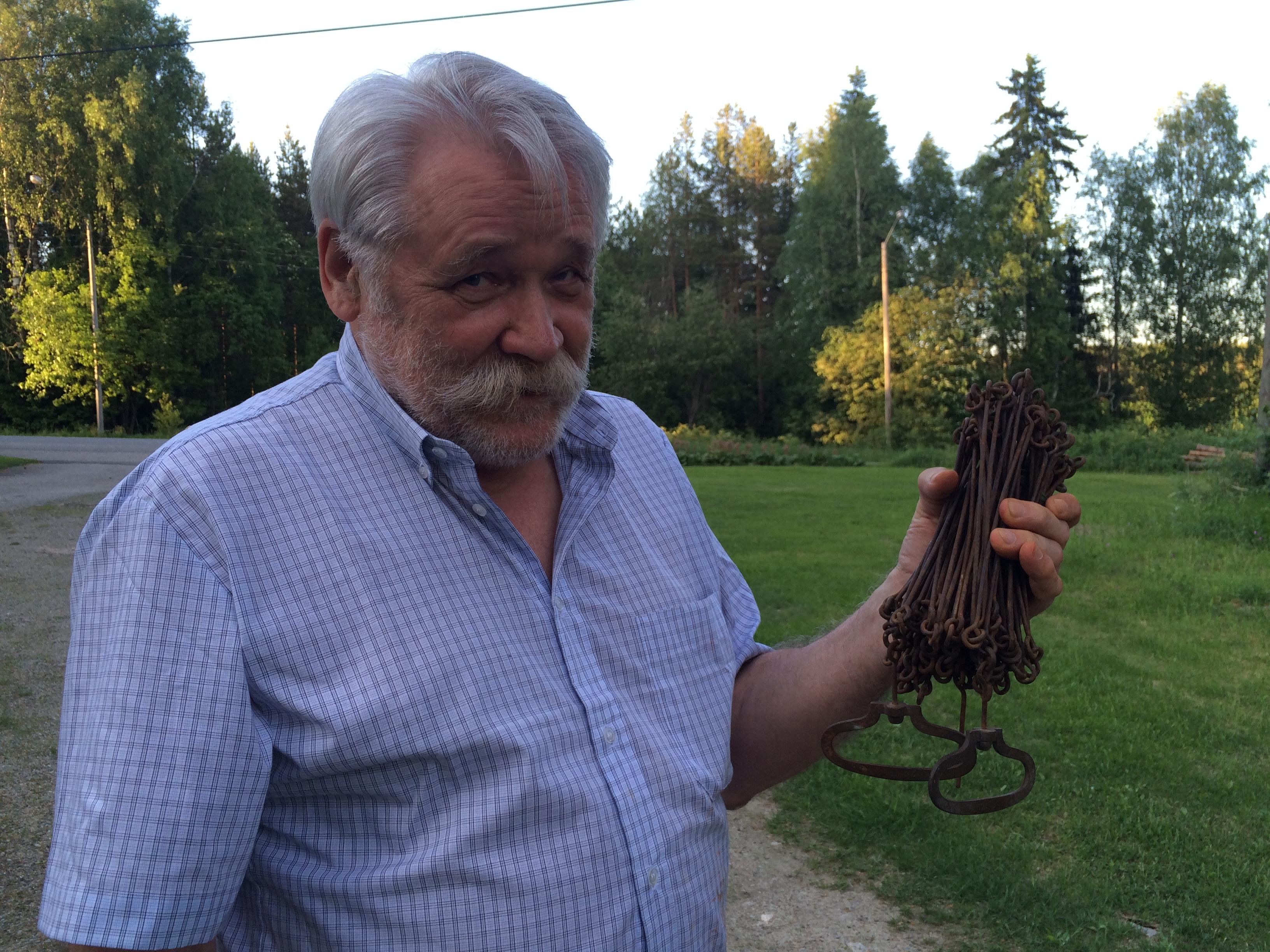 Här visar Bo-Göran Lindh upp den kätting som användes när lotterna i Storsjöträsk skulle märkas ut.