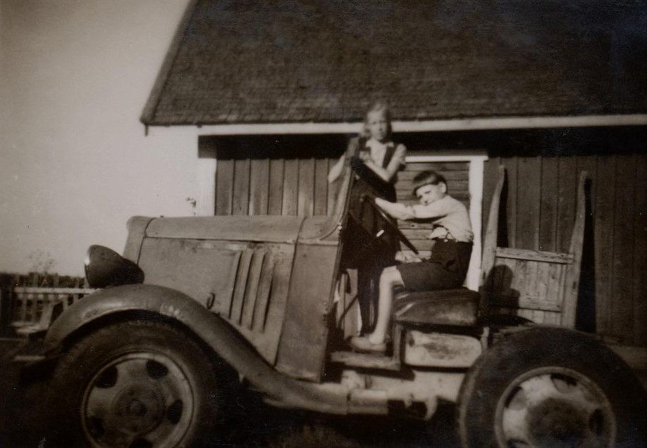 Syskonen Deris och Ralf Nyholm provsitter biltraktorn av märket Chevrolet.