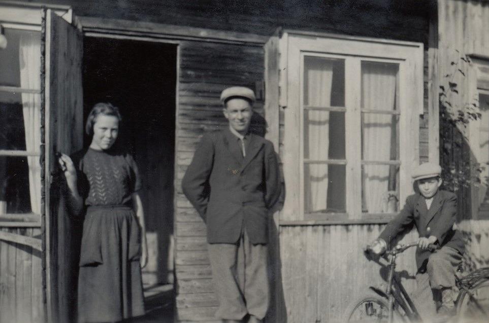 I dörren står syskonen Ellen och Ruben Ånäs. Pojken på cykeln är Ralf Nyholm och fotot av taget på Sunnantillvägen.