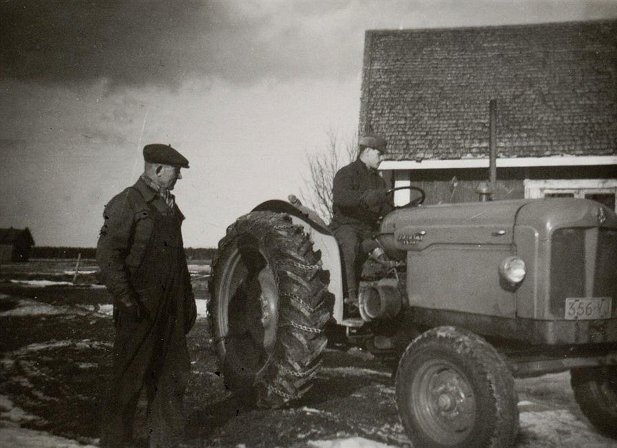 Emil Nyholm står och ser på, då mågen Lars Ålgars kör traktorn.