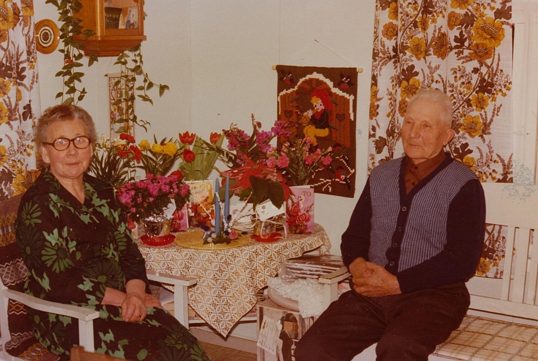Här sitter Hulda och Emil Nyholm och av korten bland blommorna att döma är det någon av dom som fyller 70.
