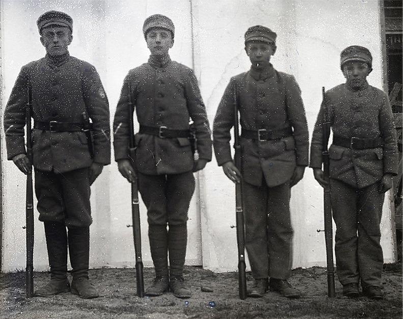 Fyra skyddskårssoldater uppställda hos fotografen Viktor Nylund. Längst till vänster står Artur Rosengren. SLS:s arkiv.