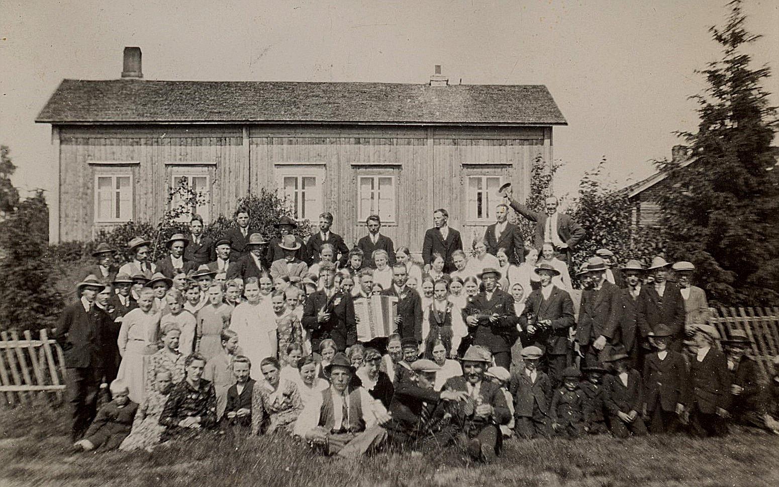 Det är svårt att urskilja brudparet Hulda Nyholm och Emil Hammarberg bland alla glada bröllopsgäster åt 1931. Nyholms gård i bakgrunden.