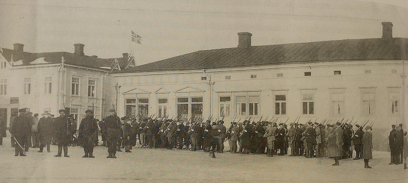 Den 31 januari 1918 var en stor dag i Kristinestads historia, då de ryska trupperna och deras bundsförvanter rödgardisterna avväpnades på morgonen efter en kort strid. Här ser vi skyddskårerna uppställda på torget den 31 januari. Flaggan i bakgrunden på Töttermans gård är den tillfälliga röda flagga med gult kors med blåvita kanter som användes en kort tid efter Finlands självständighetsförklaring.
