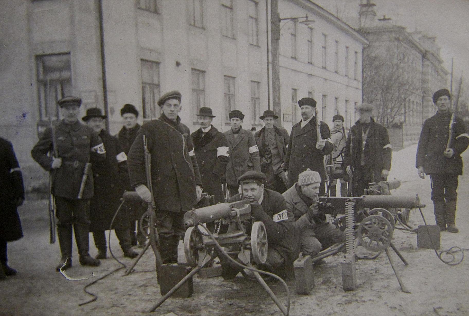 Då inbördeskriget bröt ut i slutet på januari 1918, så hade de vita trupperna inga vapen alls och inte någon militär utbildning heller för den delen. Endast ett fåtal hade uniform, så det var den vita armbindeln som visade på vilken sina trupperna stod. Vapnen på bilden som är tagen på Rådhusgatan i Vasa är sådana som beslagtagits av de ryska trupper som tidigare hade avväpnats.