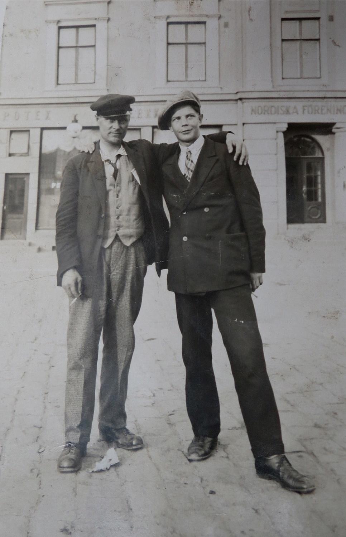 Till vänster står Emil Sved utanför Nordiska Föreningsbankens kontor på Nedre torget i Vasa någon gång på 30-talet. Mannen till höger är tillsvidare okänd.