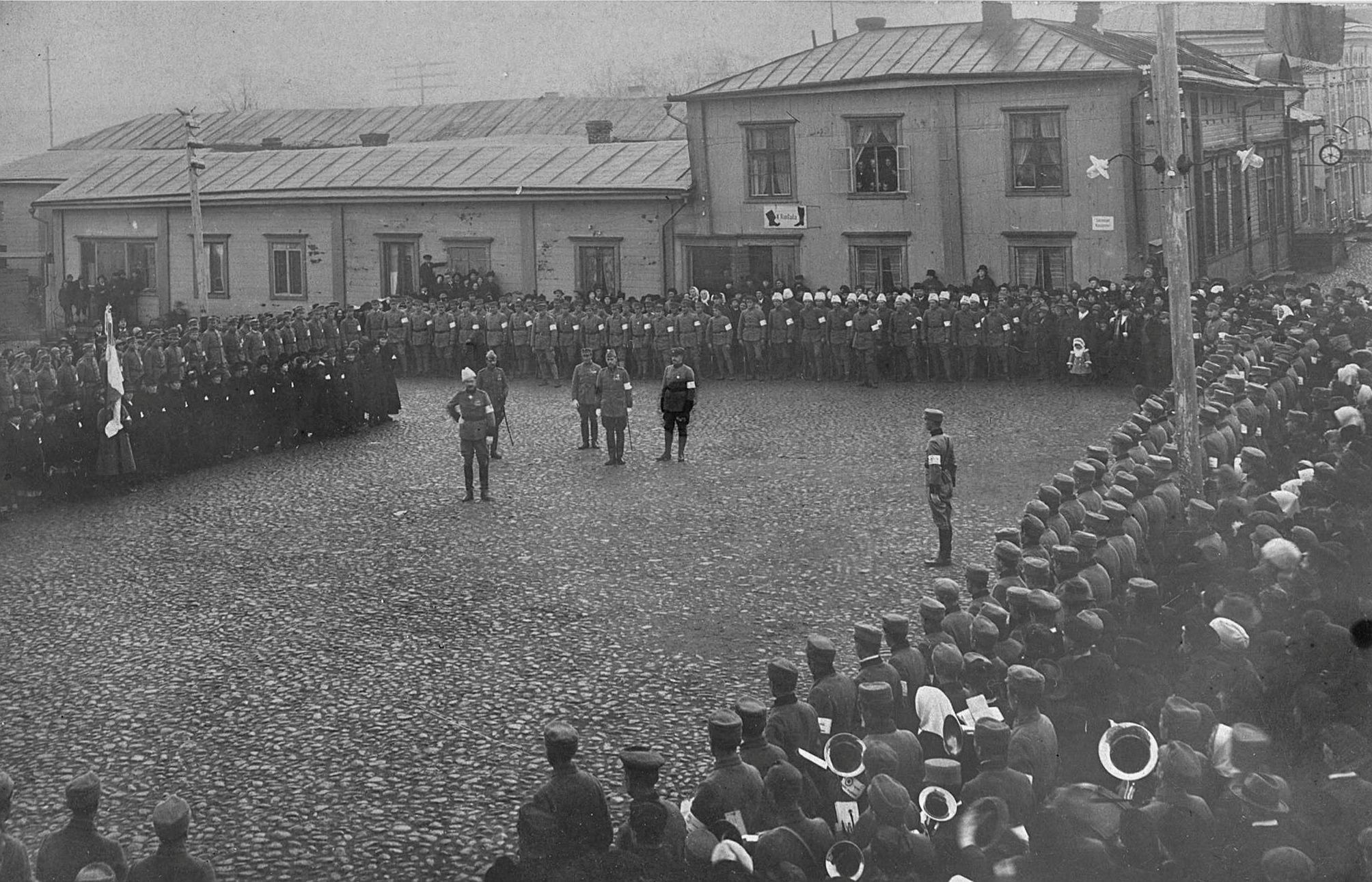 Gustav Mannerheim mönstrade skyddskårstrupperna som var samlade på Salutorget den 21 november 1920. I bakgrunden Svenska gården och troligtvis är det direktören för Ab Pärusfors Viktor Nylund med sin familj som syns i det öppna fönstret.