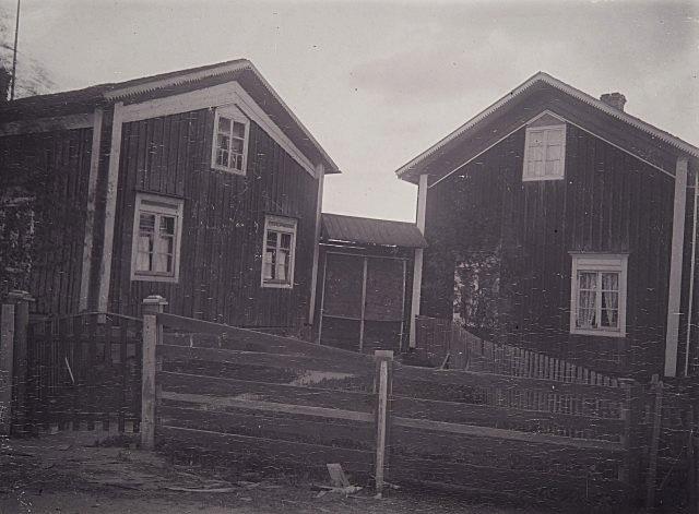 På detta foto från 1908 så ser vi en speciell port mellan de två gårdarna och därtill fanns det en grind i staketet. Byggnaden till höger revs i början på 1920-talet då den nya byggdes, men byggnaden till vänster står fortfarande kvar i originalskick. Fotot taget 20.8.1908 av A. O. Heikel och finns arkiverat på Museiverket.