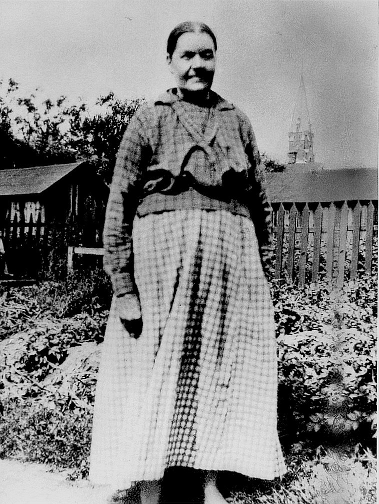 Här står Anna Kajsa Rosenback på gårdsplanen i Kristinestad. I bakgrunden skymtar Kristinestads nya kyrka. Före hon dog, bodde hon en tid i Palon i Dagsmark hos dottern Hulda Granlund.
