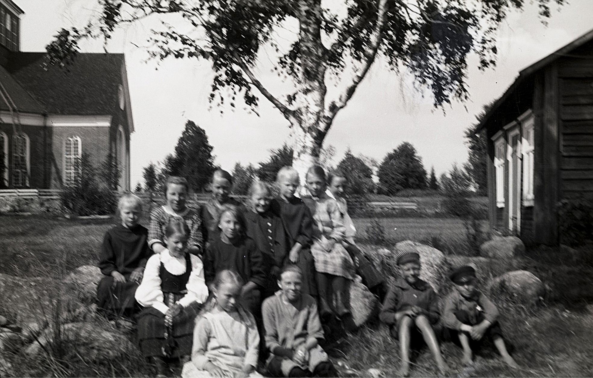 Barn på skolans gårdsplan med skolbastun till höger och kyrkan till vänster. Flickan längst fram till vänster är Ellen Asplund och bredvid henne sitter Helmi Ekman. Flickan i folkdräkt är Elin Rosenback och där bak finns bland annat Tyra Ingves, Märta Skogman, Anna Rosenback, Elin Gullmes, Svea Ådjers och Hilda Svedberg. Den av pojkarna som sitter till vänster är Karl Ådjers.