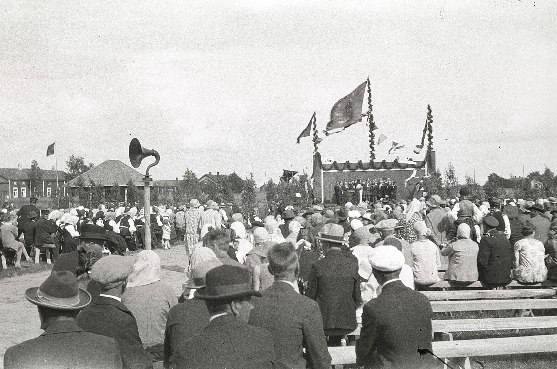 Publiken samlad för att lyssna på körsång på idrottsplanen i Lappfjärd år 1930. Notera speciellt högtalaren.