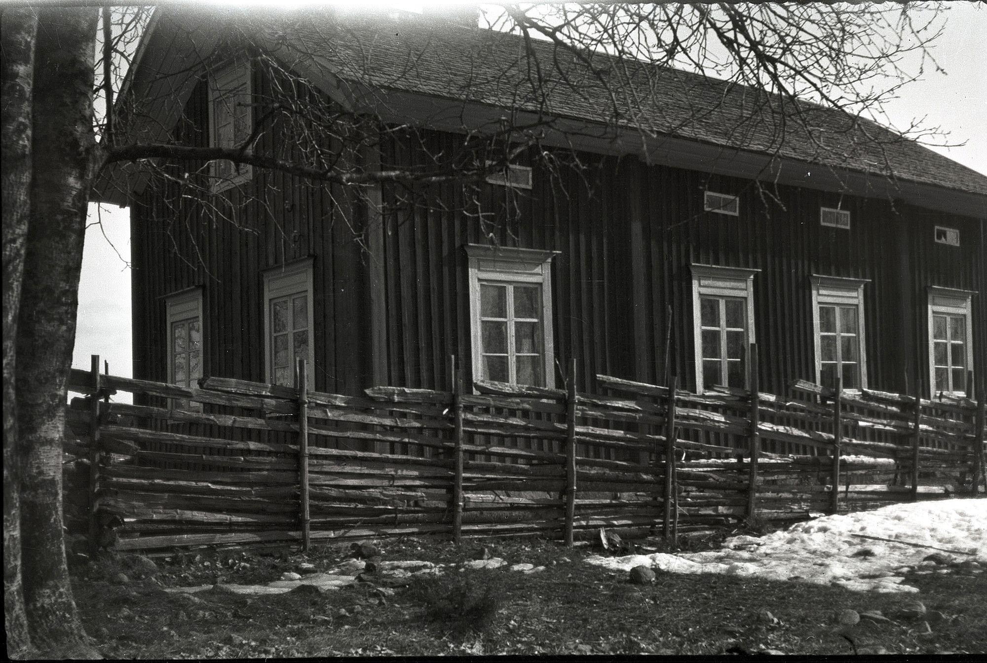 """Småbarnskolan på Kladdbackan fram till år 1933. Lärarinnans bostad till vänster och själva skolsalen till höger. Här ett bra exempel på en riktig gärdesgård eller """"jeisgål"""" som den kallades på dialekt. Först slog man ner """"stevoran"""" och så radade man i """"trodorna"""" som sedan bands fast med """"stölingan"""" som var små kluvna granstammar."""