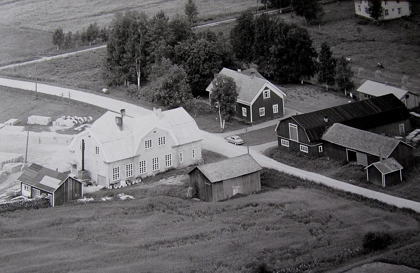 Den stora tegelbyggnaden till vänster är Dagsmark Andelsmejeris byggnad från 1929 men som när detta foto togs 1961 ägdes av Ragnar och Verna Långfors. De bodde i övre våningen och i bottenvåningen tillverkade de tellblock av cement. Mejeribyggnaden förstördes i en brand sommaren 1977. På andra sidan Åbackvägen står Krook-gården som just detta år övertogs av Boris och Gun-Lis Långfors. Den stora uthusbyggnaden med mansardtak förstördes i en brand sommaren 1966 och efter det byggdes de uthus som fortfarande står kvar. Uppe i högra hörnet syns lite av Storkulls gård.