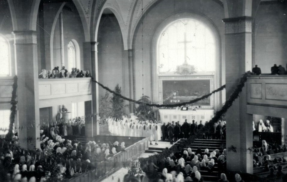 Konfirmanderna står i dubbla rader framför altaret i Lappfjärds kyrka. Ett par dagar på förhand hämtade konfirmanderna enris i skogen, som de dekorerade kyrkan med. Altaret dekorerades med björkar, som man gjorde förr i midsommartid.